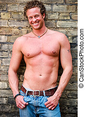 Tough guy - A well built, muscular man stands next to a wall