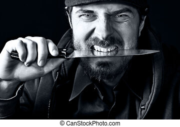 Tough guy with knife - Tough angry guy biting from sharp...