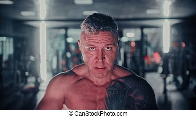 Tough man with gray hair training his hands in the gym. Mid ...