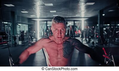 Tough man with gray hair training his hands in the gym using...