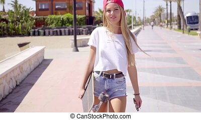 Tough young blond skateboarder walking on sidewalk