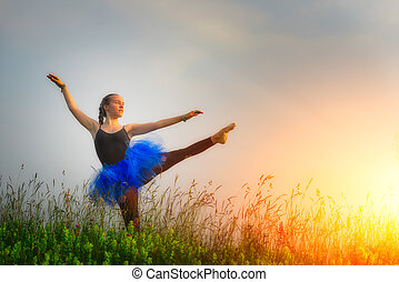Toung beautiful ballerina dancing outdoors