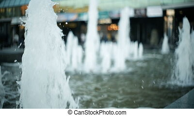 Toung blonde woman is walking in the city, passing by the fountain, moving from the camera Back view