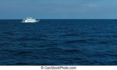 Tour Boat Traversing a Tropical Seascape - White tour boat...