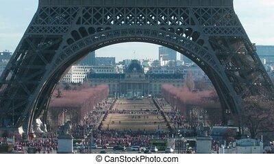 Tour Eiffel keeps away. Movement under Tour Eiffel in a current of day: cars, tourists. Paris, France. Time lapse.