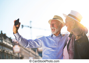 Tourism and technology. Traveling senior couple taking selfie together against sightseeing background.