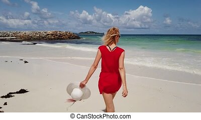 Tourism at Anse Kerlan - Happy tourist woman holding hand of...
