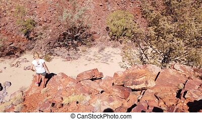 Carefree woman after Ghost Gum walk overlooking Ormiston Gorge in Central Australia. West Mac Donnell Ranges, Northern Territory, Outback Red Center.