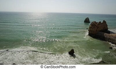 Tourism in Portugal, Europe. Top sandstone rocks of Praia do Pinhao in Lagos on Algarve coast. In the distance the famous Dona Ana Beach. Aerial view of Pinhao Beach.