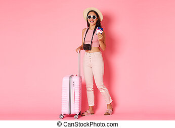 Tourism, summer vacation, holidays abroad concept. Full length of trendy asian girl tourist, traveller in hat and sunglasses packed suitcase and holding passport with flight tickters, pink background