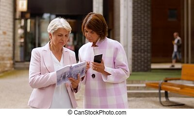 tourism, travel and friendship concept - happy senior women with city guide and smartphone on tallinn street