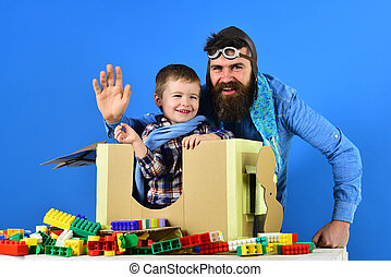 Tourism travel, goodbye flight. Son and father, games for children young age. Toys to develop motor skills. Father plays with his young son. Attributes of aviation on blue background. Flight by plane