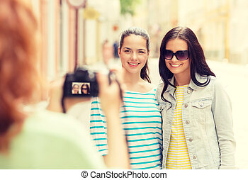 smiling teenage girls with camera - tourism, travel,...