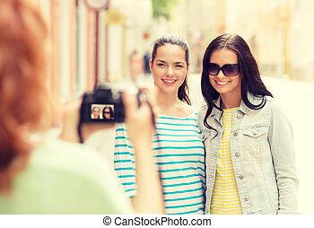 smiling teenage girls with camera - tourism, travel,...