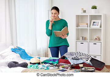 woman with notebook planning her trip at home