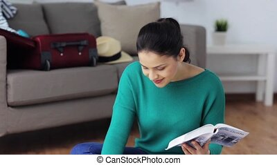 woman with city guide preparing for travel at home -...