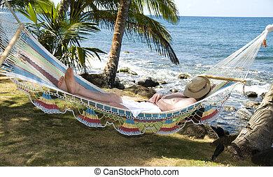 tourist asleep in hammock by the caribbean sea