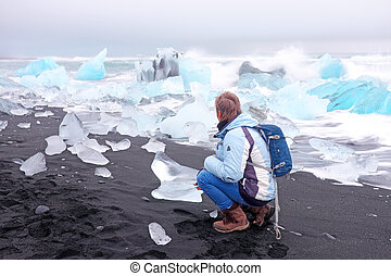 Tourist at ice rocks on the black sand beach in Iceland