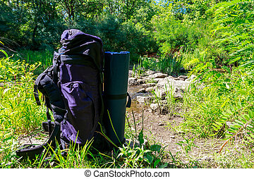 Tourist backpack near a river at summer. Hike concept