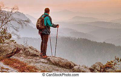 Tourist backpacker in mountains. Autumnal foggy weather