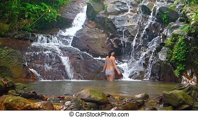 Tourist Bathing in Pool beneath Natural Waterfall