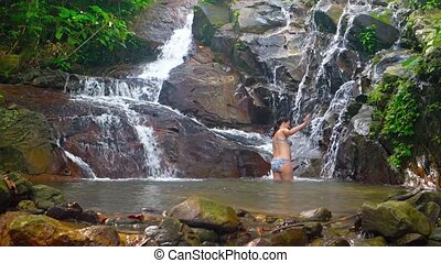 Happy tourist, bathing in the cool, refreshing water at the base of a natural waterfall, at a nature preserve in Southeast Asia. Video 3840x2160