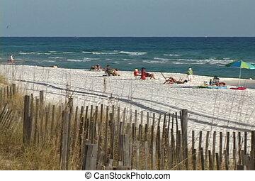 Pan across the beach shows tourists relaxing under the sun on Destin Beach, Florida.
