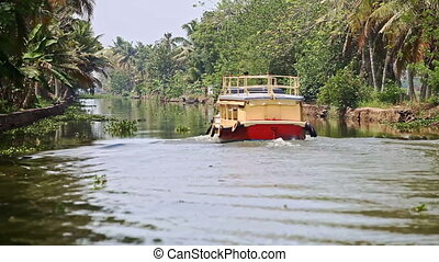 Tourist Boat Moves away along River with Palm Banks in...