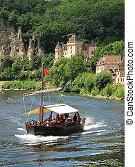 Boat cruising down the Dordogne past La Roque Gageac, France