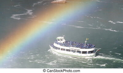 tourist boat passes under a rainbow, niagara falls, usa and canada