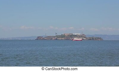 Tourist boat sails near the island of Alcatraz. Alcatraz...