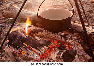 Tourist breakfast at dawn. Bonfire, bowler with food and tripod. Wooden firewood, coals, summer on nature in the forest. Delicate colors of the morning sun.