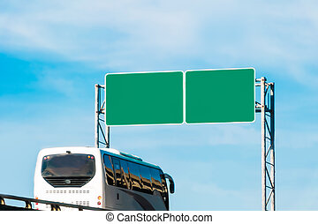tourist bus and blank green traffic road sign
