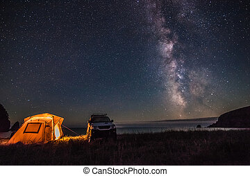 Tourist camping at sea coast at night with milky way. Some...
