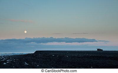 Tourist car and blue icebergs in Jokulsarlon beach, full moon