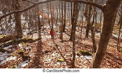 Tourist carries the kayak to the water in the forest.
