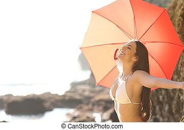 Happy tourist celebrating good weather breathing fresh air on a beach holding an umbrella on summer