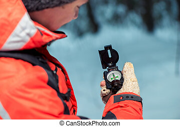 tourist checks the route with a compass in the winter forest