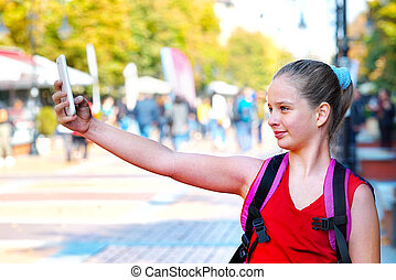 Tourist child girl with backpack taking selfies on smartphone