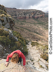 Tourist climbing cliff in the Golden Gate Highlands National Park, South Africa. Adventure and exploration in Africa.