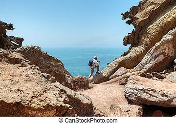 Tourist climbs the rock to make good shot of nature.