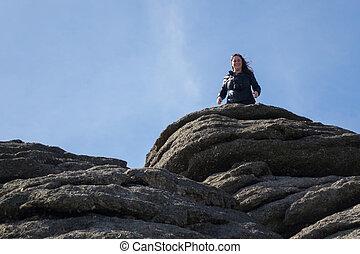 Tourist climbs up the granite slopes of Haytor Rocks - ...