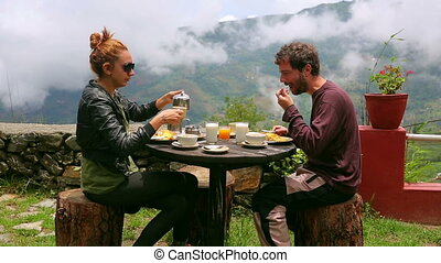Tourist couple eating breakfast in himalayas mountains at Nagarkot, Kathmandu, Nepal