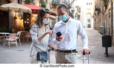 Tourist couple in medical masks to prevent respiratory infection consulting navigation app in cellphone during walk around city