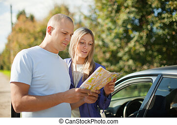 tourist couple looking at the map on road