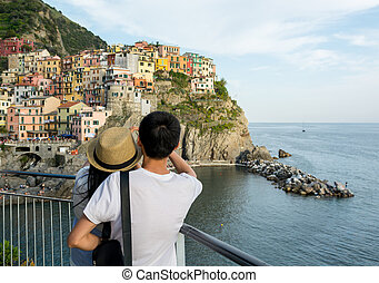 Tourist couple looking at traditional port town embraced in a hug.
