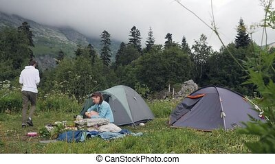 Tourist couple resting on camping tent in mountain...