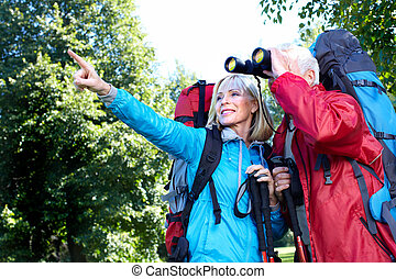 Tourist couple. - Senior Tourist couple with backpacks in...