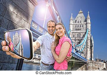 Tourist couple taking selfie against Tower Bridge in London, England, UK