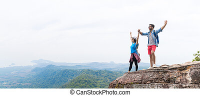 Tourist Couple With Backpack Holding Hands Raised On Mountain Top Enjoy Beautiful Landscape Panorama